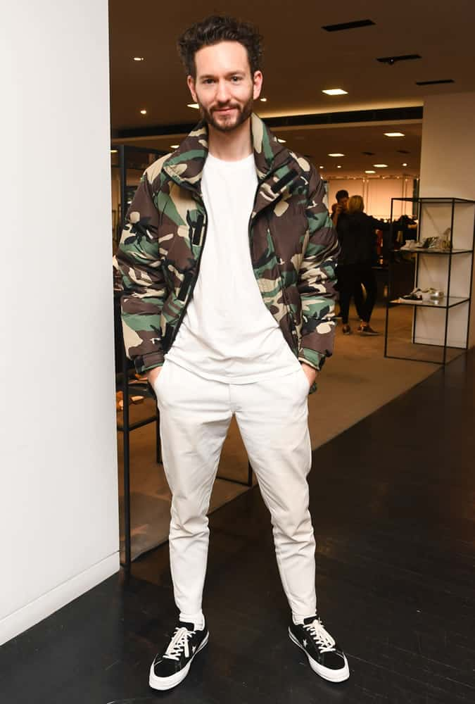 Isaac Hinin-Miller dressed in a white outfit with a camouflage jacket